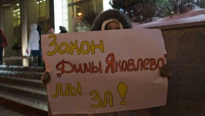 """A demonstrator holds a poster reading """"We are for Dima Yakovlev Bill"""" outside the Federation Council on Wednesday, Dec. 26, 2012.  (AP / Alexander Zemlianichenko)"""
