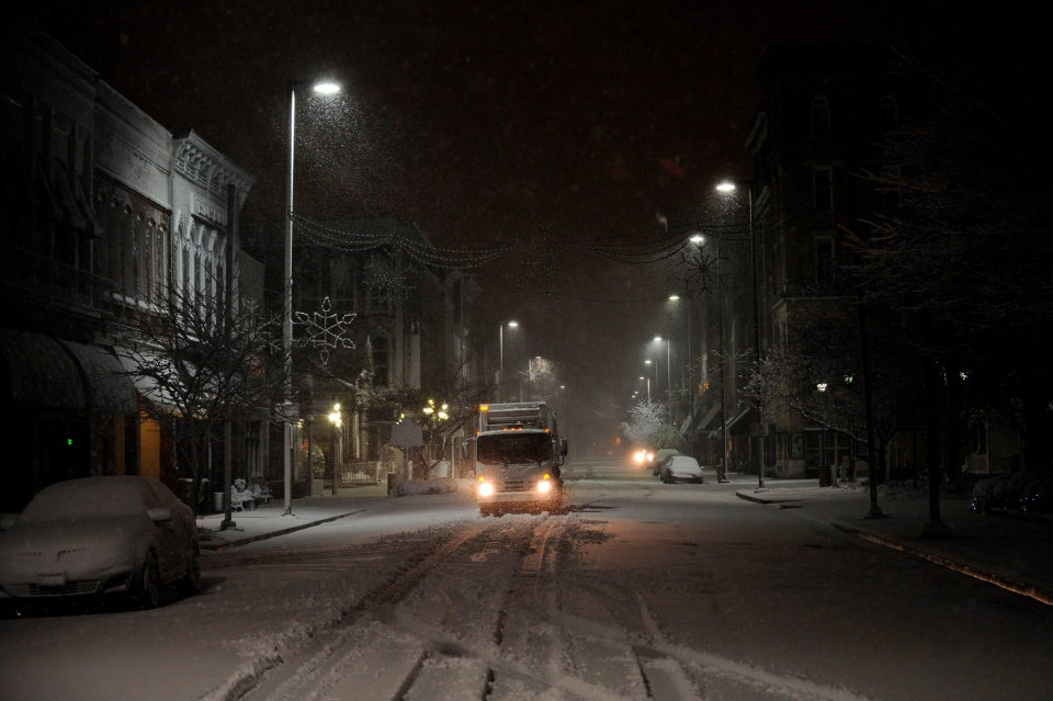 A city waste management truck drives on Broadway in Paducah, Ky. while collecting trash downtown during a winter storm Wednesday, Dec. 26, 2012. (AP / Stephen Lance Dennee)