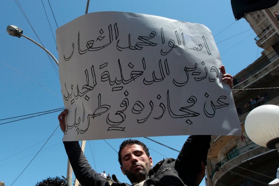 "A supporter of an Islamic group, holds up an Arabic placard read: ""Ask the new Syrian Interior Minister Mohammed al-Shaar about his massacres in Tripoli,"" as he protests against Syrian regime, in the northern city of Tripoli, Lebanon, on Friday April 22, 2011. (AP / Hussein Malla)"