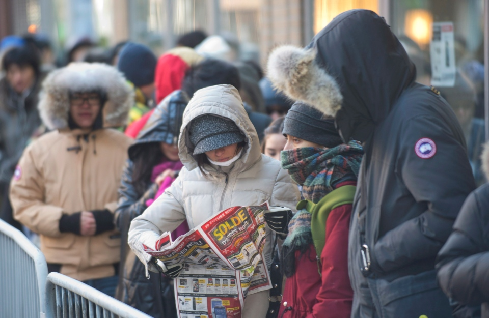 A woman looks at a flyer offering big discounts while queuing outside an electronics store on Boxing Day in Montreal on Wednesday, Dec. 26, 2012. (Graham Hughes / THE CANADIAN PRESS)