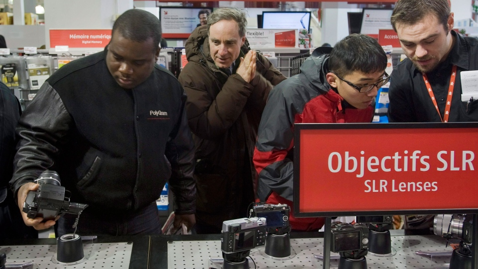 Shoppers look at cameras at an electronics store during the annual boxing day sale in Montreal, Monday, December 26, 2011. (Graham Hughes / THE CANADIAN PRESS)