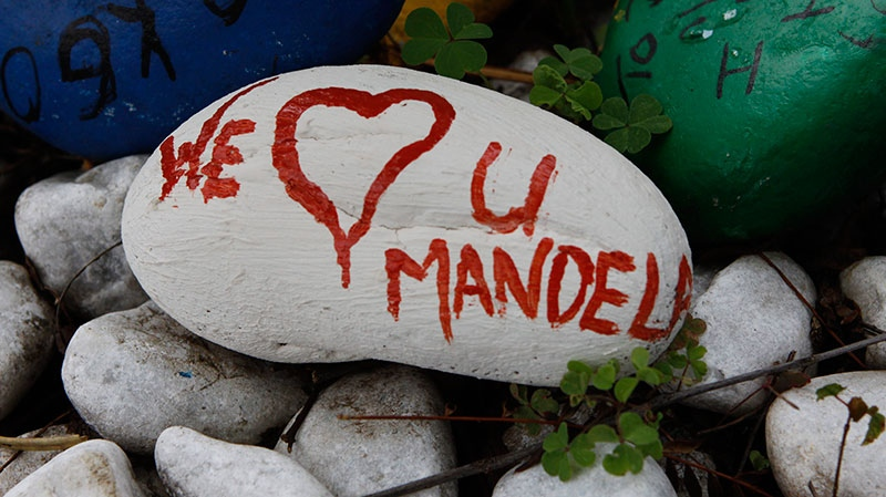 A pebble with a message to former President Nelson Mandela lays outside his Johannesburg home Thursday, Dec. 27 2012. (AP / Denis farrell)