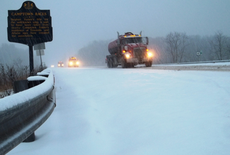 Trucks travel down a snowy Route 6 near the intersection with Route 409, between Wyalusing, Pa. and Towanda, Pa., during the snowstorm late Wednesday afternoon, Dec. 26, 2012. (AP / The Daily Review, Nancy Sharer)