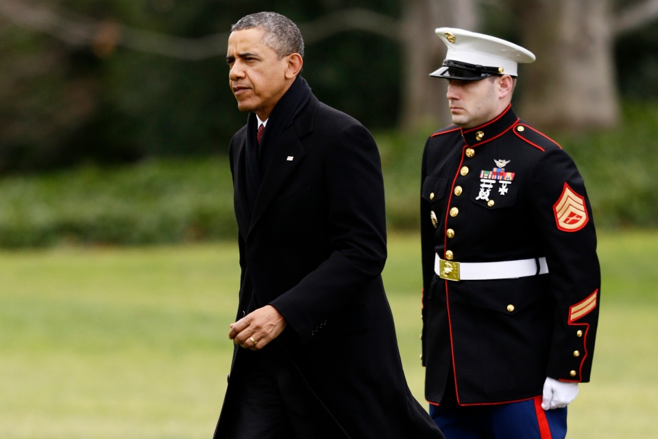 U.S. President Barack Obama walks past a Marine honor guard as he steps off the Marine One helicopter and walks on the South Lawn at the White House in Washington, Thursday, Dec. 27, 2012, as he returned early from his Hawaii vacation for meetings on the fiscal cliff. (AP / Charles Dharapak)