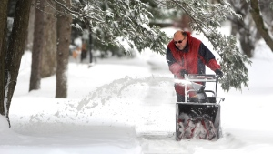 Terry Baney ducks under a branch as he removes snow from his driveway with a snowblower, in State College, Pa., Thursday, Dec. 27, 2012. (AP / Centre Daily Times, Nabil K. Mark)