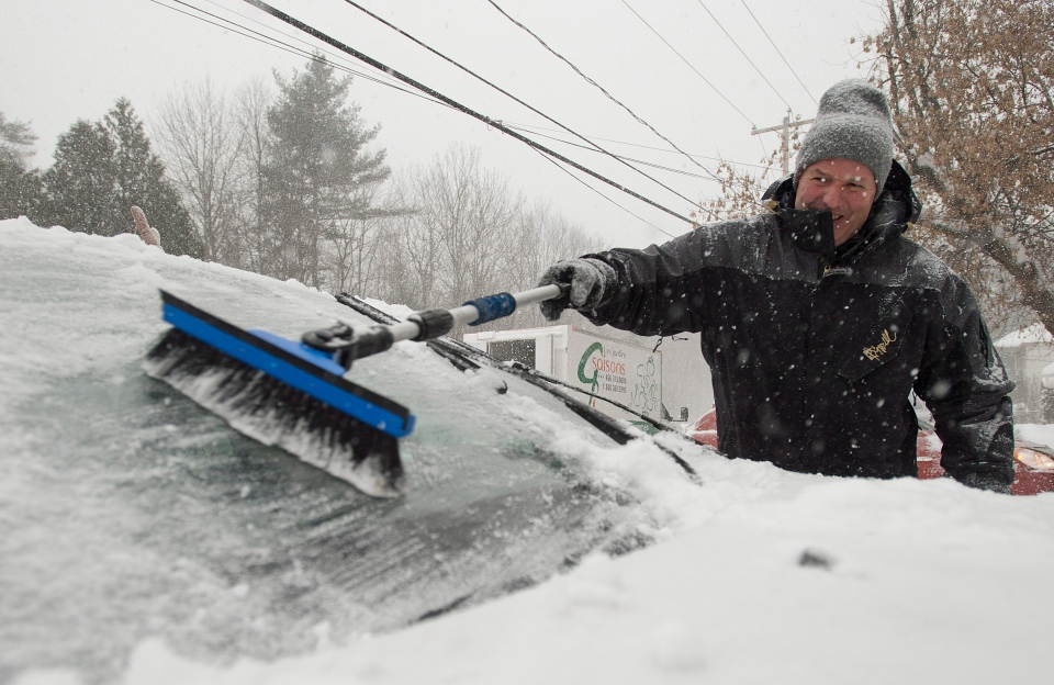 Peter Johnson clears snow from his car near Montreal, Thursday, Dec. 27, 2012. (Graham Hughes / THE CANADIAN PRESS)