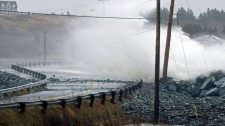 Waves roll over the breakwater on the causeway in Cow Bay, N.S. on Dec. 6, 2010. (Andrew Vaughan / THE CANADIAN PRESS)