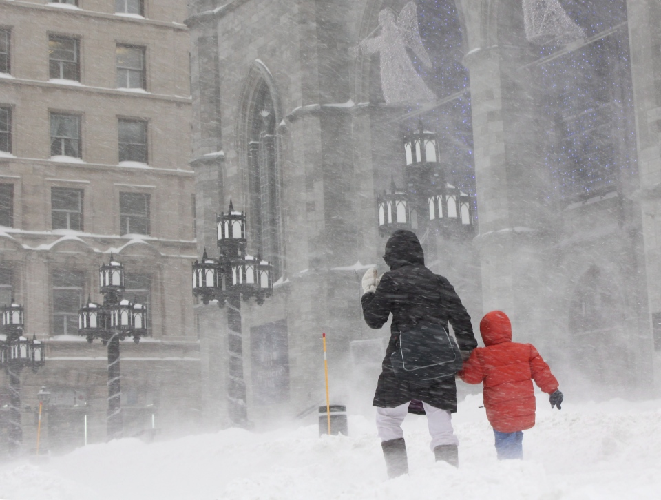 A woman walks with her child in past Notre-Dame Basilica in Old Montreal on Thursday Dec. 27, 2012. A winter storm is disrupting travel plans in Eastern Canada, with winds whipping up visibility-stifling, traffic-snarling clouds of white.THE CANADIAN PRESS/Alexander Panetta