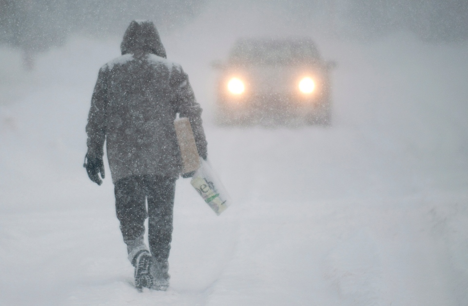A man walks along a road near Montreal Thursday, Dec. 27, 2012 during the first major snowstorm of winter in the region. THE CANADIAN PRESS/Graham Hughes.