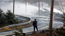 An unidentified man takes a a photo as waves roll over the breakwater on the causeway in Cow Bay, N.S. on Dec. 6, 2010. (Andrew Vaughan / THE CANADIAN PRESS)
