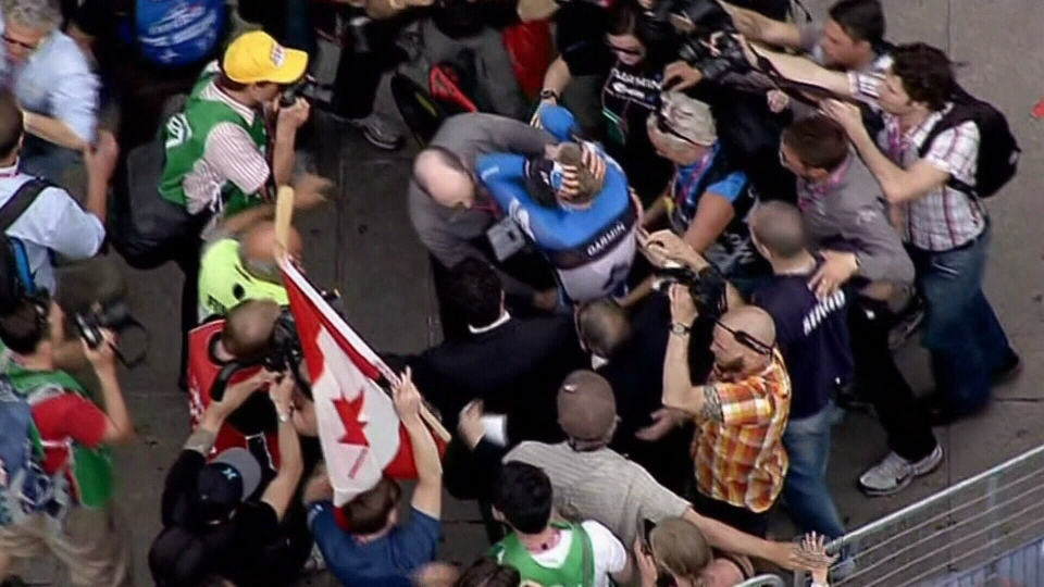 Canadian cyclist Ryder Hesjedal is swarmed by fans and press in this file photo.