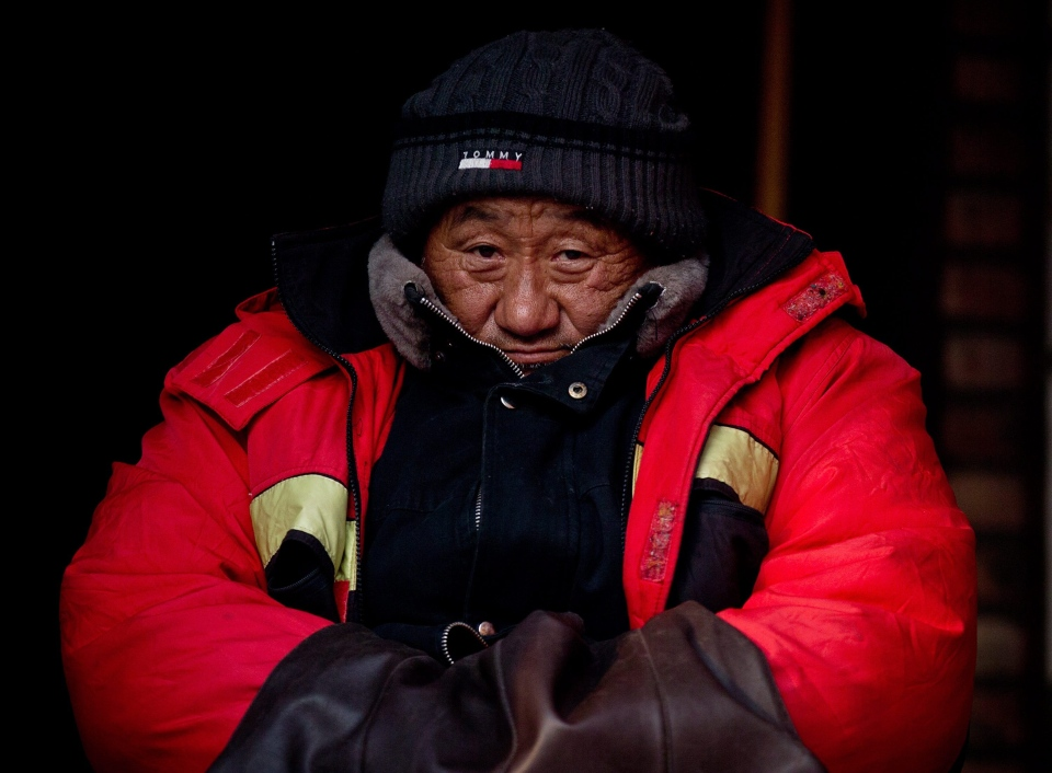 An elderly street worker wearing thick winter clothes rests outside a courtyard house along a Hutong alley in Beijing Wednesday, Dec. 26, 2012. (AP / Andy Wong)