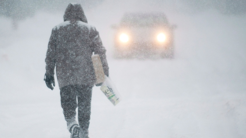 A man walks along a road near Montreal during the first major snowstorm of winter in the region Thursday, Dec. 27, 2012. (Graham Hughes / THE CANADIAN PRESS)