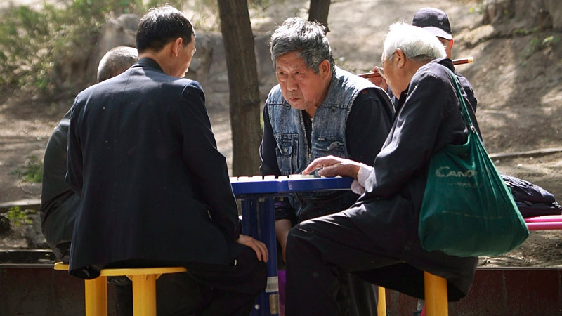 Elderly men play chess at a park in downtown Beijing, China, Thursday, April 26, 2012. (AP Photo/ Vincent Thian)