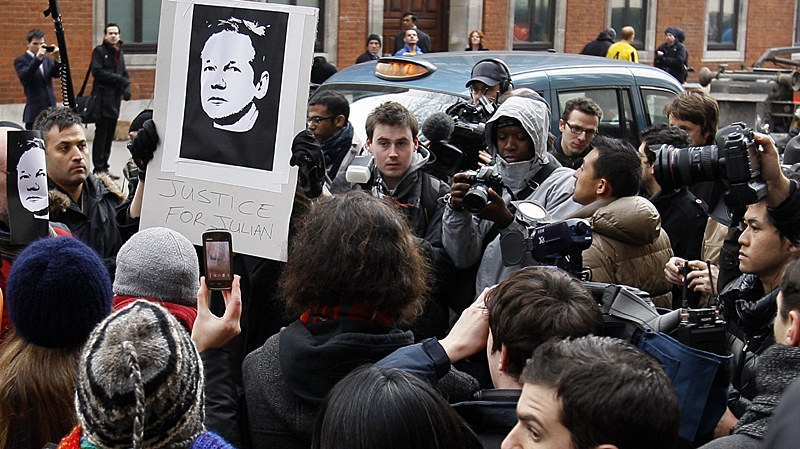 Members of the media gather around a demonstrator near Westminster Magistrates Court in London, Tuesday, Dec. 7, 2010. (AP / Kirsty Wigglesworth)