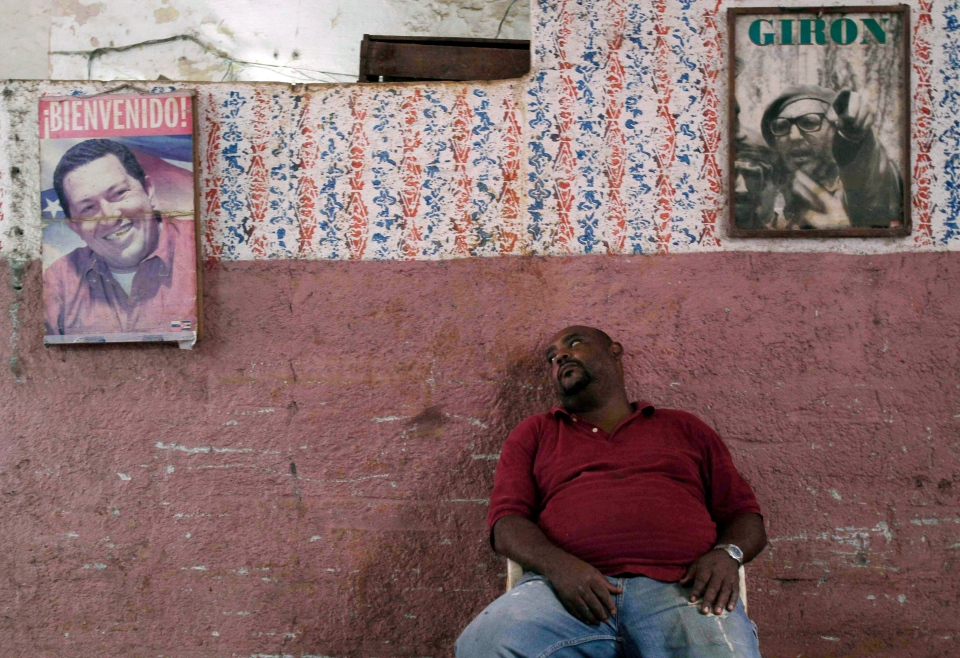 A worker who sells vegetables takes a rest against a wall featuring posters of Venezuela's President Hugo Chavez, left, and former Cuban leader Fidel Castro, in Havana, Cuba, Dec. 10, 2012. (AP / Franklin Reyes)