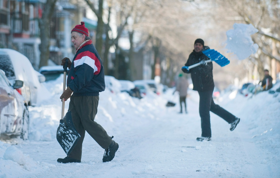Maurice Desrosiers, left, digs out his car in Montreal, Friday, Dec. 28, 2012. (Graham Hughes / THE CANADIAN PRESS)