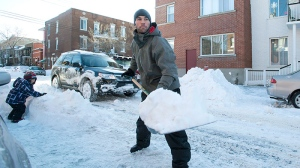 Pascal Morin with son Derek digs out his car in Montreal, Friday, Dec. 28, 2012, following the first major snowstorm of winter in the region. (Graham Hughes / THE CANADIAN PRESS)