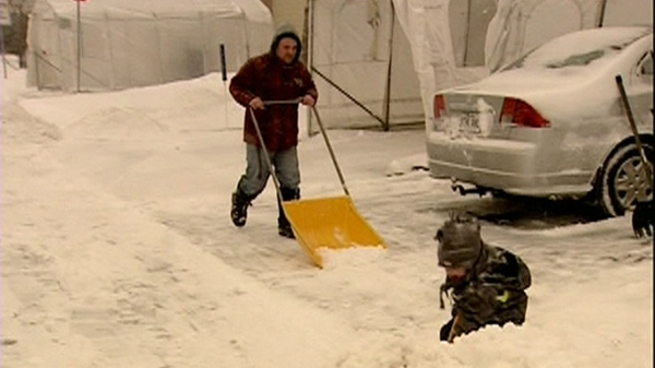 The whole family gets involved in clearing driveways during Montreal's first storm of the season. (Dec. 7, 2010)