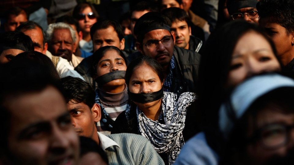 Women wear black bands across their face as they join a gathering mourning the death of a gang rape victim in New Delhi, India, Saturday, Dec. 29, 2012. (AP / Saurabh Das)