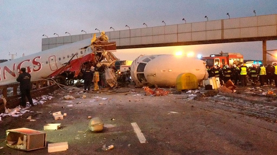 Rescuers work at the site of a plane that careened off the runway at Vnukovo Airport in Moscow, Saturday, Dec. 29, 2012. (AP / Alexander Usoltsev)
