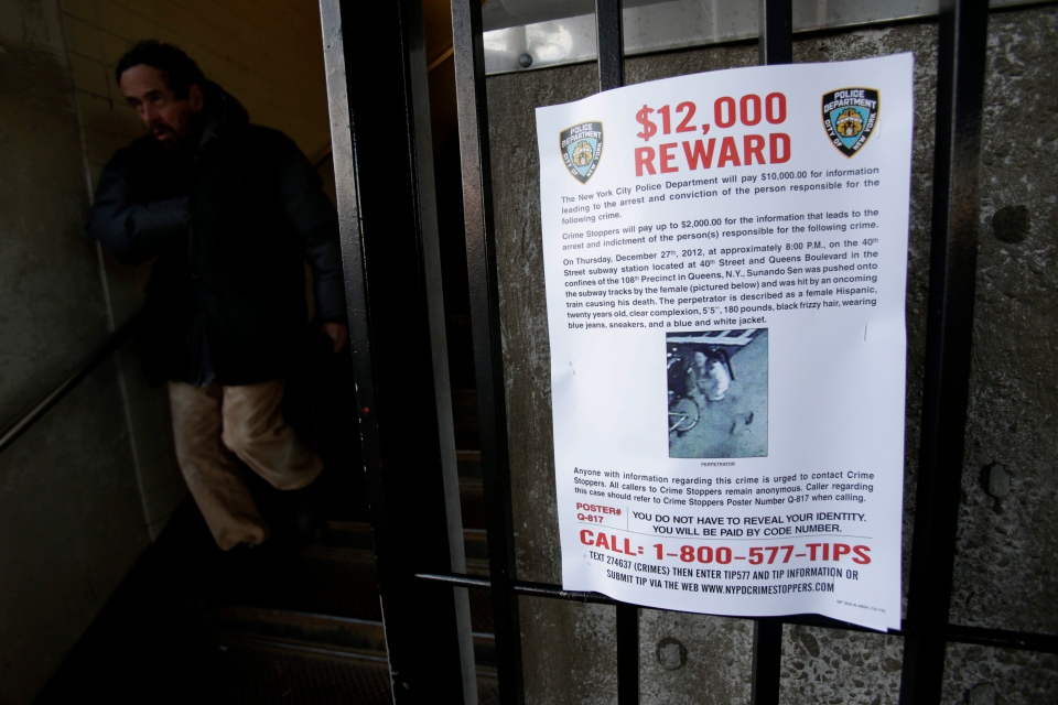 A reward poster is displayed on the entrance to the 40th St-Lowry St Station, where a man was killed after being pushed onto the subway tracks, in the Queens section of New York, Friday, Dec. 28, 2012.  (AP / Seth Wenig)