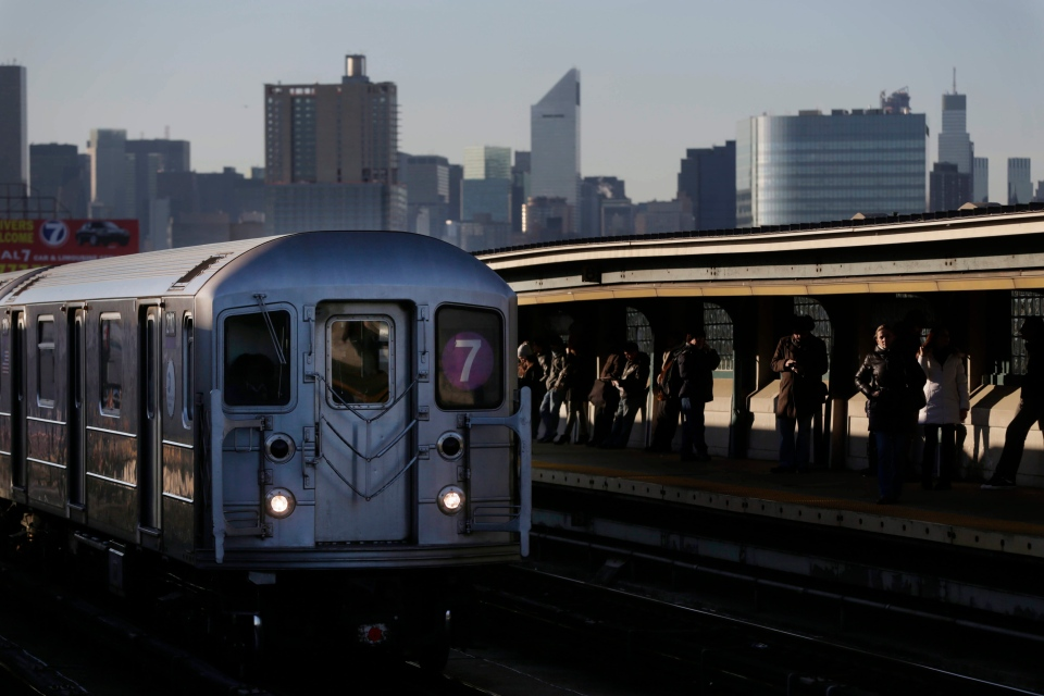 Commuters wait on the platform as a train passes through the 40th St-Lowry St Station, where a man was killed after being pushed onto the subway tracks, in the Queens section of New York, Friday, Dec. 28, 2012. (AP / Seth Wenig)