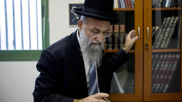 Israeli Rabbi Mordechai Nagari who recently signed a religious ruling barring Jews from selling or renting homes to non-Jews, takes a book from his cabinet in his office as he poses for a photo, in the Jewish West Bank settlement of Maaleh Adumim near Jerusalem, Tuesday, Dec. 7, 2010. (AP / Tara Todras-Whitehill)