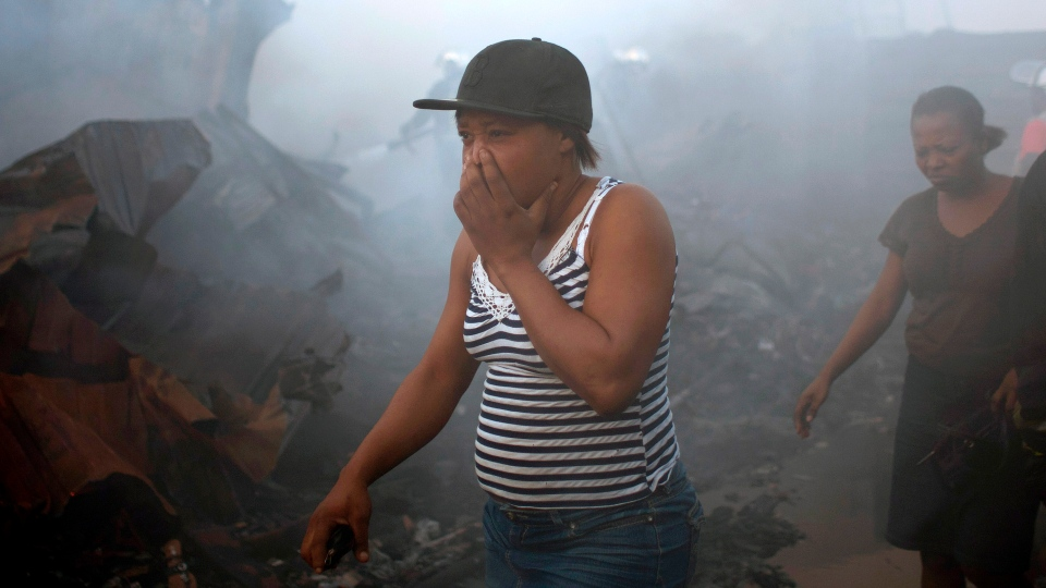 A woman covers her mouth and nose as she walks past charred vending stalls at the smoke-filled Port Market in Port-au-Prince, Haiti, Saturday Dec. 29, 2012. (AP / Dieu Nalio Chery)