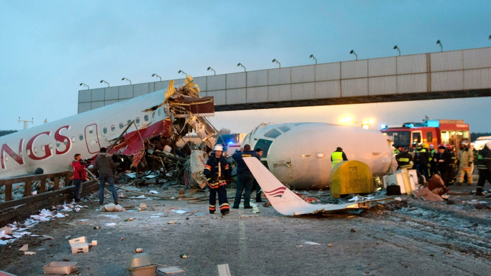 Rescuers work at the site where a plane careered off the runwaw at Vnukovo Airport in Moscow, Saturday, Dec. 29, 2012. (AP / Alexander Usoltsev)