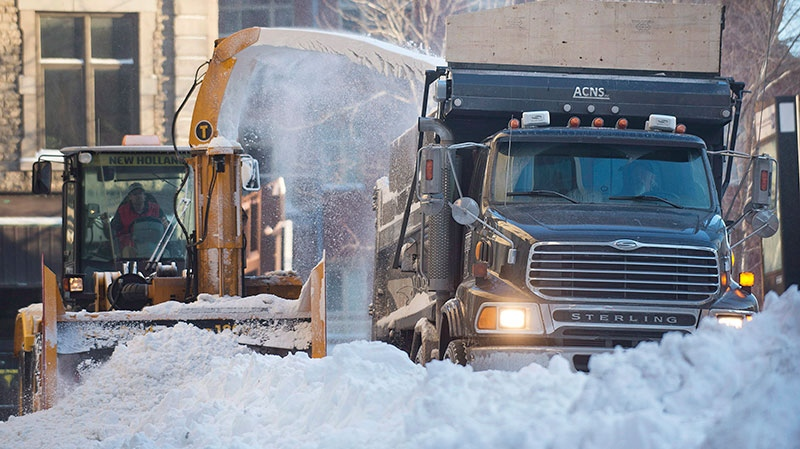 A snow removal crew clears a street in Montreal, Friday, Dec. 28, 2012, following the first major snowstorm of winter in the region. (Graham Hughes / THE CANADIAN PRESS)