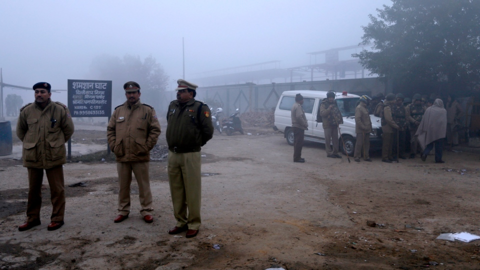 Policemen stand guard outside the crematorium as the last rites for a 23-year-old rape victim are performed, in New Delhi, India, Sunday, Dec. 30, 2012. (AP / Saurabh Das)