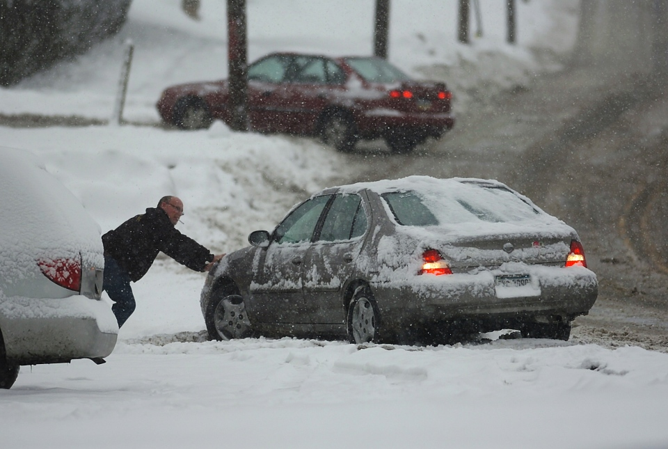 A resident helps out a motorist push his car out of the snow on an icy West Lackawanna Avenue in Blakely, Pa. on Saturday, Dec. 29, 2012. The same storm system is heading north towards eastern Canada.  (Scranton Times & Tribune, Butch Comegys)