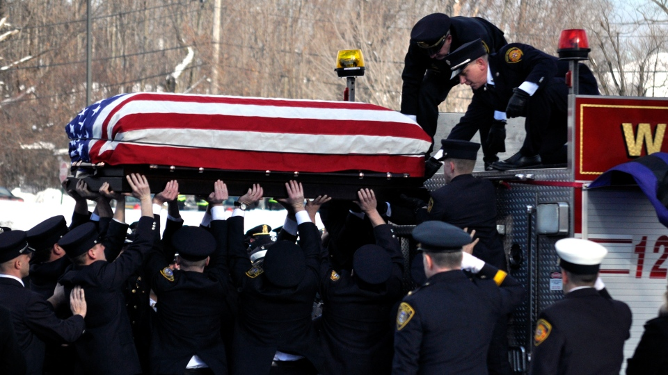 The flag covered casket of Lt. Mike Chiapperini is lowered into place at the start of a funeral service in Webster, N.Y., Sunday, Dec. 30, 2012. (AP / Kevin Rivoli)