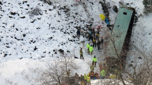 Emergency personnel respond to the scene of a multiple fatality accident where a tour bus careened through a guardrail along an icy Oregon highway and fell several hundred feet down a steep embankment, authorities said, about 15 miles east of Pendleton, Ore., Sunday, Dec. 30, 2012. (East Oregonian, Tim Trainor)