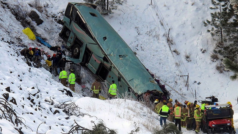 Emergency personnel respond to the scene of a multiple-fatality accident after a tour bus careened through a guardrail along an icy highway and fell several hundred feet down a steep embankment, authorities said, about 15 miles east of Pendleton, Ore., Sunday, Dec. 30, 2012.  (East Oregonian, Tim Trainor)