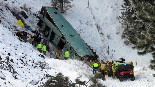 Emergency personnel respond to the scene of a deadly crash where a tour bus careened through a guardrail along an icy highway and down a steep embankment east of Pendleton, Ore., on Sunday, Dec. 30, 2012. (AP / East Oregonian, Tim Trainor)