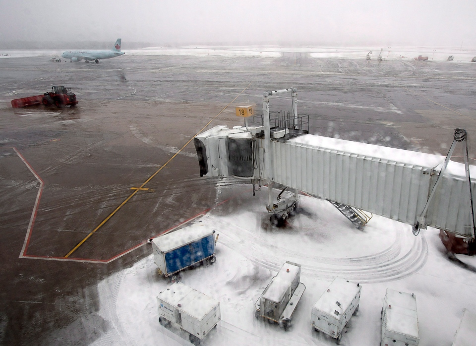 A snowplow works on the runway at Halifax Stanfield International Airport in Enfield, N.S. on Sunday, Dec.30, 2012 as a winter storm passed through the region. (Andrew Vaughan / The Canadian Press)