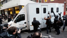 Members of the media gather around a prison van as it leaves the rear entrance of Westminster Magistrates Court in London, Tuesday, Dec. 7, 2010. (AP / Kirsty Wigglesworth)