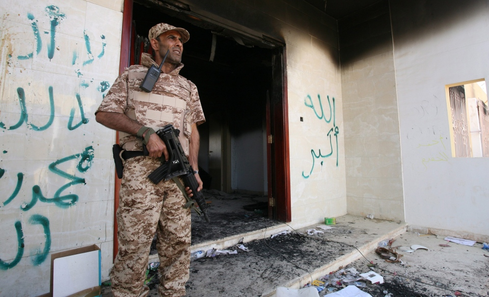 This Sept. 14, 2012 file photo shows a Libyan military guard standing in front of one of the U.S. Consulate's burnt out buildings during the visit of President Mohammed el-Megarif, not shown, to the U.S. Consulate, in Benghazi, Libya. (AP / Mohammad Hannon)