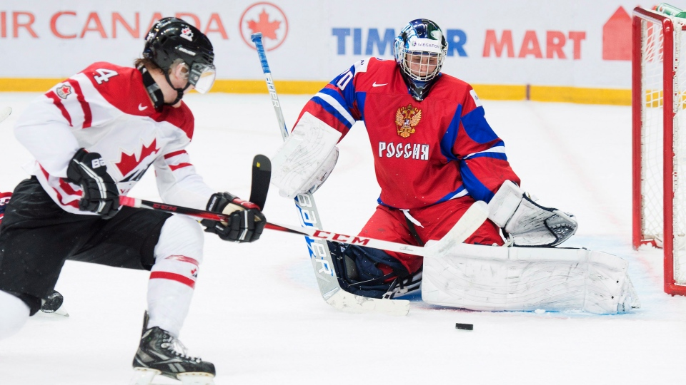 Team Canada defenceman Morgan Rielly, left, is stopped by Russia goalie Andrei Makarov, right, during second period IIHF World Junior Championships hockey action in Ufa, Russia on Monday, Dec. 31, 2012. (Nathan Denette/ THE CANADIAN PRESS)
