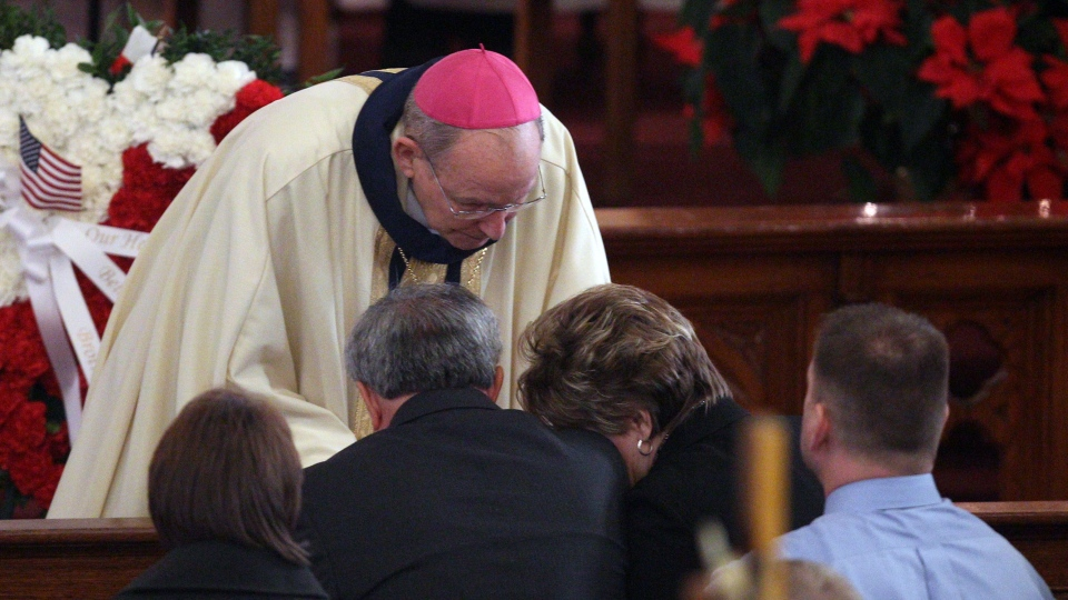 Bishop Emeritus Matthew H. Clark, shares his condolences with Marian and Janina Kaczowka during the funeral mass for their son, West Webster firefighter Tomasz Kaczowka at St. Stanislaus Church in Rochester, N.Y. Monday, Dec. 31, 2012. (Democrat and Chronicle, Jamie Germano)