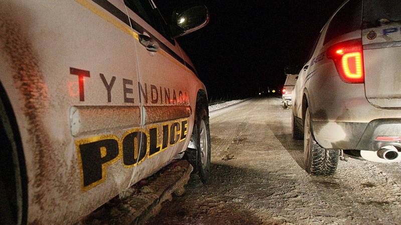 Tyendinaga police keep an eye on native protesters blocking a CN rail line in Tyendinaga, east of Belleville, Ont., on Sunday, Dec. 30, 2012. (Lars Hagberg / THE CANADIAN PRESS)