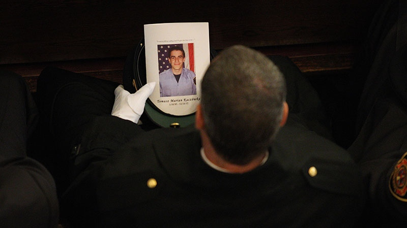 A West Webster firefighter carries a program during the funeral for fellow West Webster firefighter Tomasz Kaczowka at St. Stanislaus Church in Rochester, N.Y.,, Monday Dec. 31, 2012. (Democrat and Chronicle, Jamie Germano)