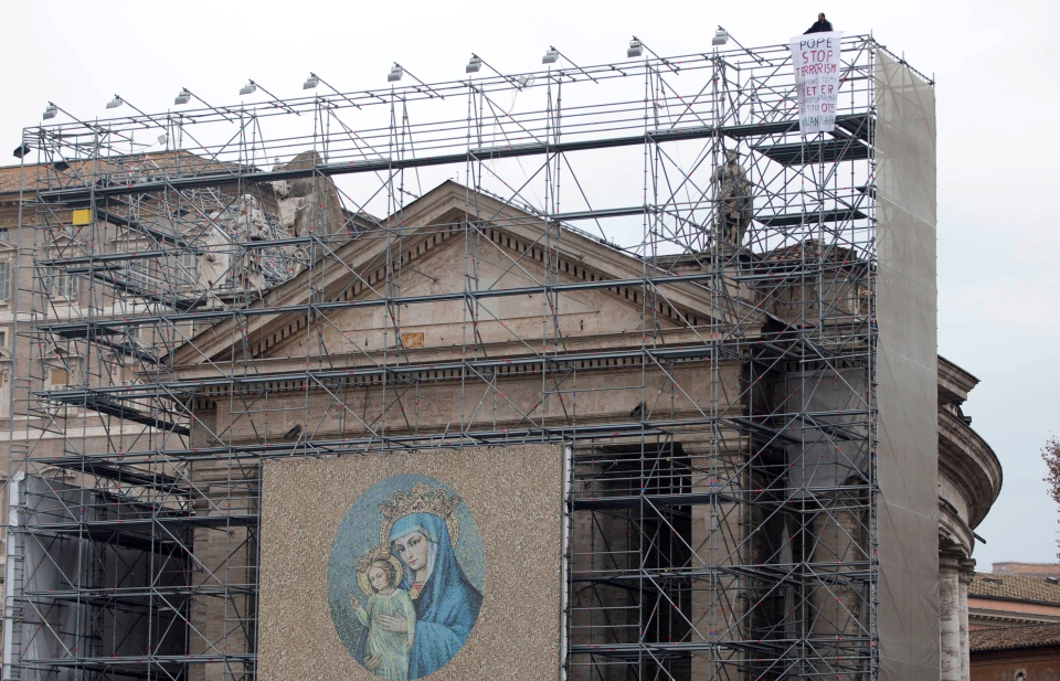 "A man identified as Julian Jungarean stands on scaffolding displaying a ""Stop Terrorism"" banner during a New Year's Day Mass celebrated by Pope Benedict XVI in St. Peter's Basilica at the Vatican, on Tuesday, Jan. 1, 2013. (AP Photo/Andrew Medichini)"