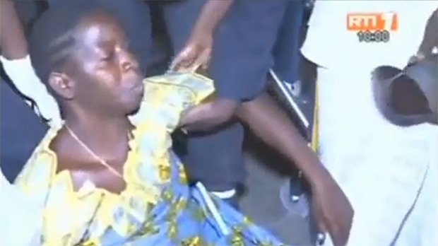 In this screen grab, an injured woman is lifted onto her feet after a deadly stampede in Abidjan, Ivory Coast, early Tuesday, Jan. 1, 2013.