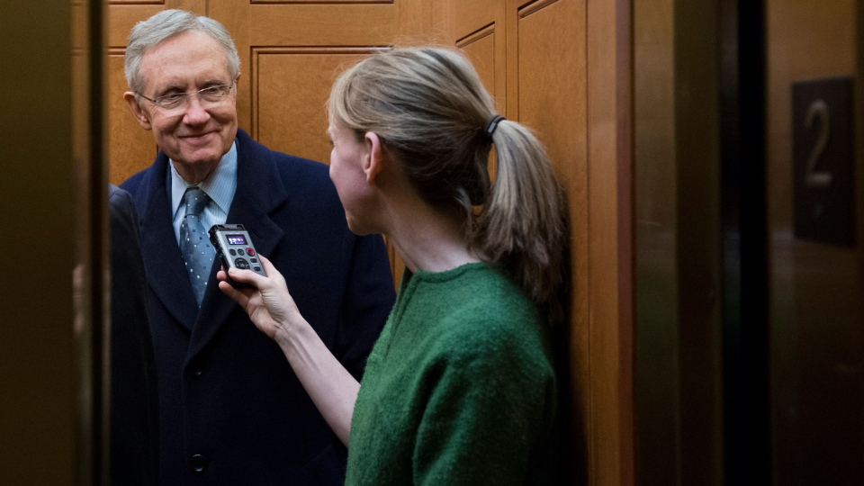 U.S. Senate Majority Leader Harry Reid, left, from Nevada, talks with a journalist as the elevator doors close as he departs the Capitol after a vote about the fiscal cliff, on Capitol Hill Tuesday, Jan. 1, 2013 in Washington.  (AP / Alex Brandon)