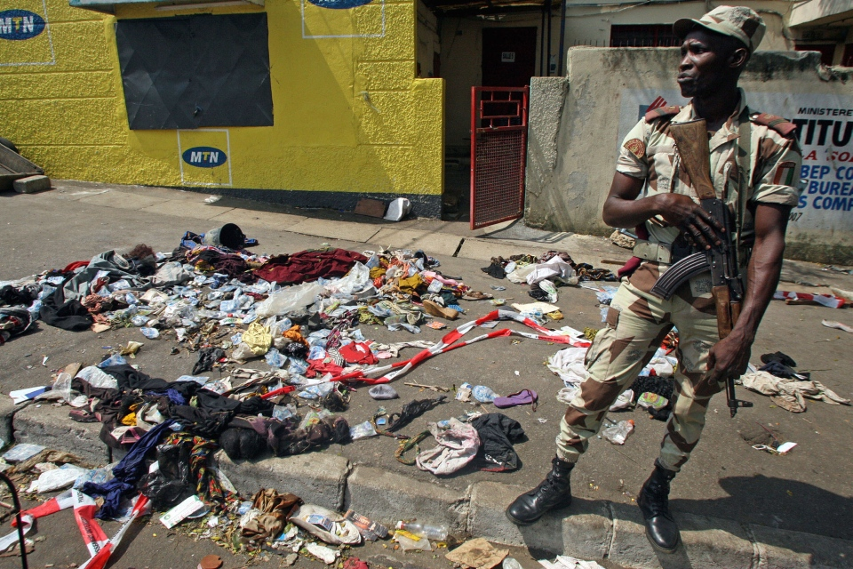 An Ivory Coast soldier stands next to the belongings of people involved in a deadly stampede in Abidjan, Ivory Coast, on Tuesday, Jan. 1 2013. At least 61 people were killed early Tuesday in a stampede following a New Year's fireworks display, said officials. (AP Photo/Emanuel Ekra)