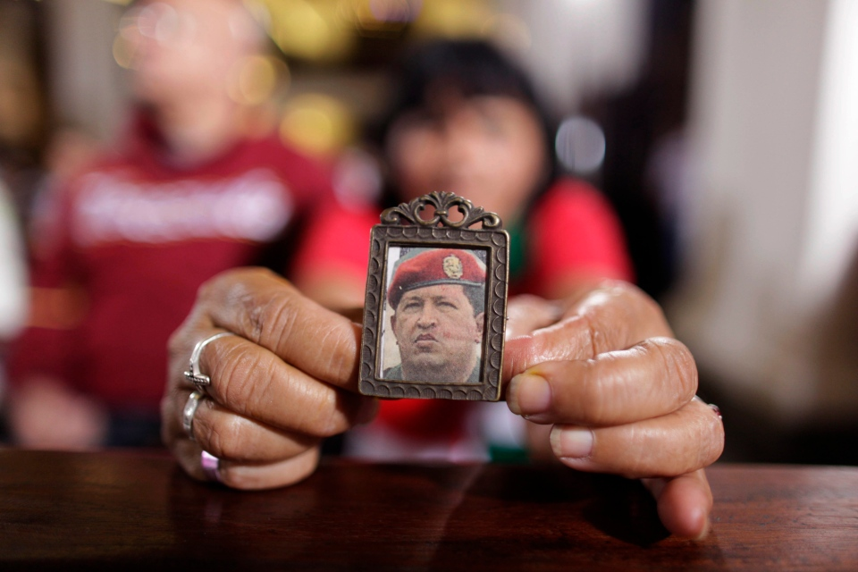 A woman holds an image of Venezuela's President Hugo Chavez as people gather to pray for him at a church in Caracas, Venezuela, Monday, Dec. 31, 2012.  (AP / Ariana Cubillos)