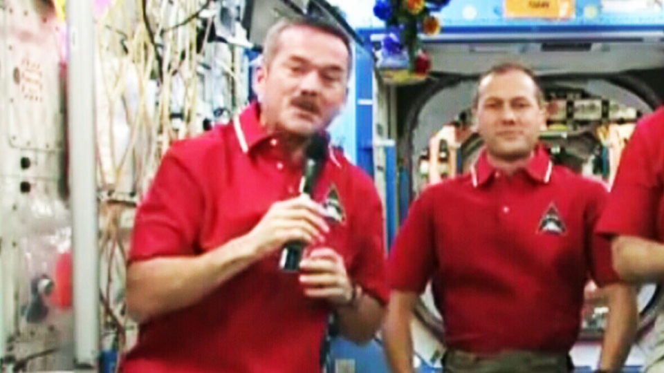 Canadian astronaut Chris Hadfield, left, takes a moment to send his New Year greetings from space from the International Space Station on Tuesday, Jan. 1, 2012.